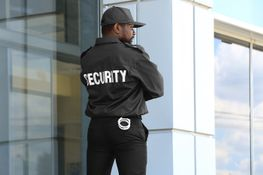 Security guard touching an earpiece, listening to information